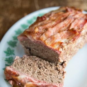 Top down shot of Sliced BaconMeatloaf in White Plate with Green Leaves Prints