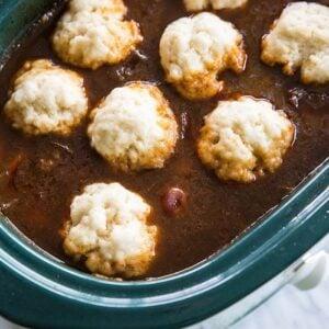 little dough dumplings on a crock pot full of soup