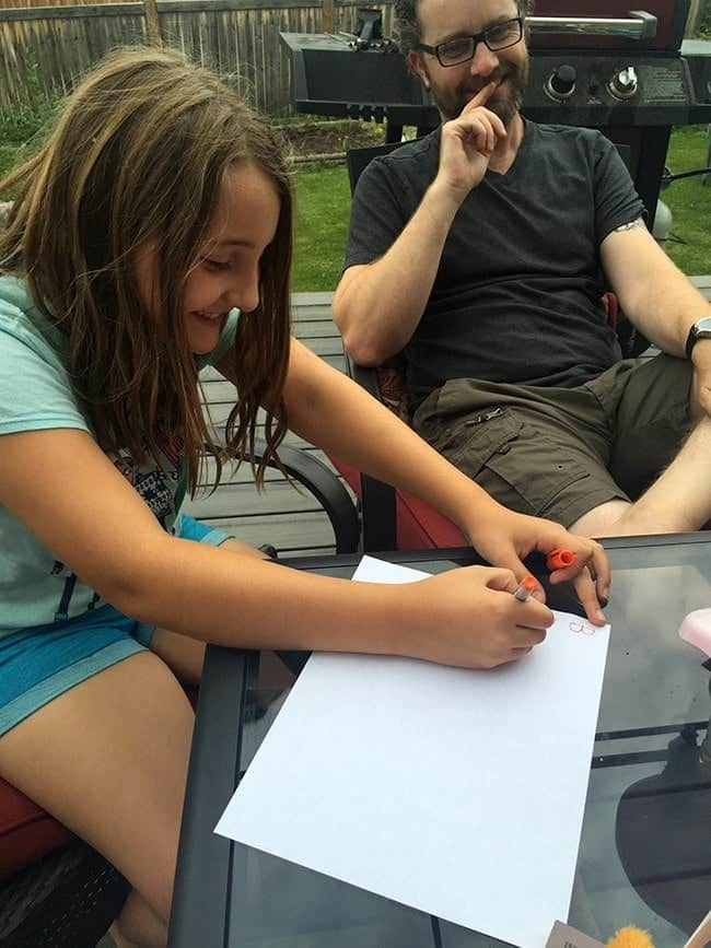 daughter sitting and writing something on a piece of white paper while his father sitting beside