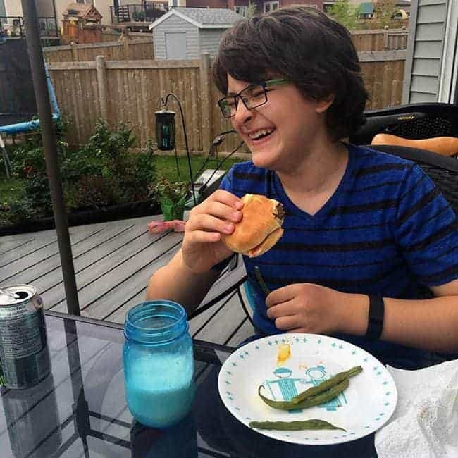 young boy in eye glasses laughing while sitting and holding a burger