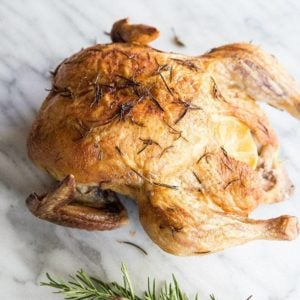Whole Roasted Chicken with Lemon and Rosemary on a marble background