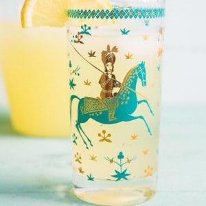 close up of Sparkling Honey Bourbon Lemonade in a glass with Arabian design garnish with a slice of Lemon