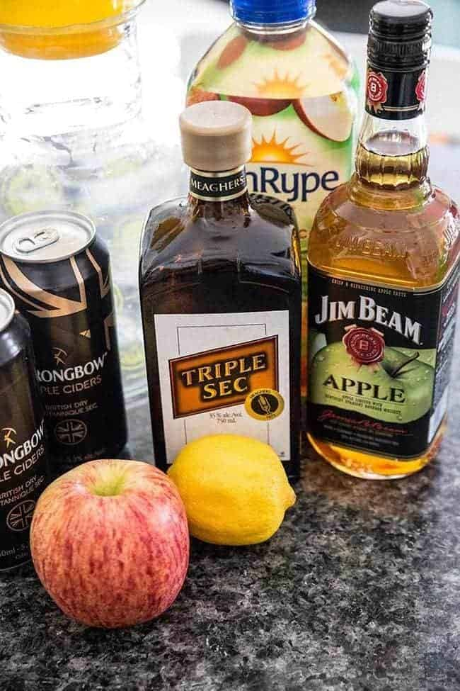bottle of apple Bourbon and triple sec together with cans of hard apple cider, fresh apple and lemon