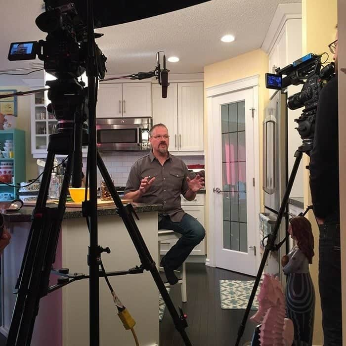 man sitting in the kitchen in front of cameras