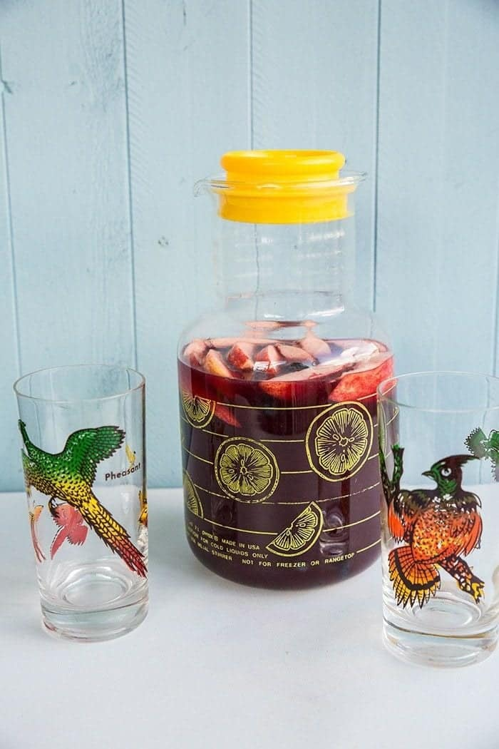 2 empty vintage glasses and a large pitcher with lid containing Red Wine Sangria