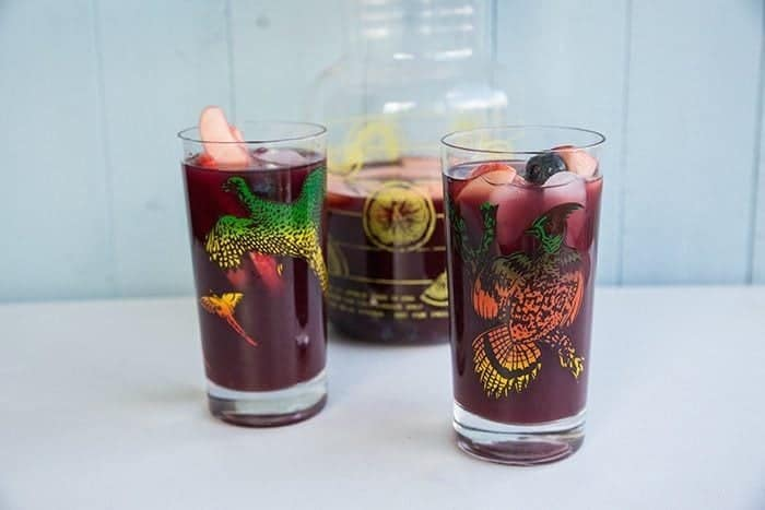 2 vintage glasses with Red Wine Sangria and a large pitcher with lid on background