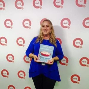 woman in front of QVC wall holding cook cook recipe