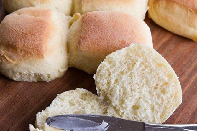 close up spreading honey butter into Sweet Dinner Rolls using spread knife