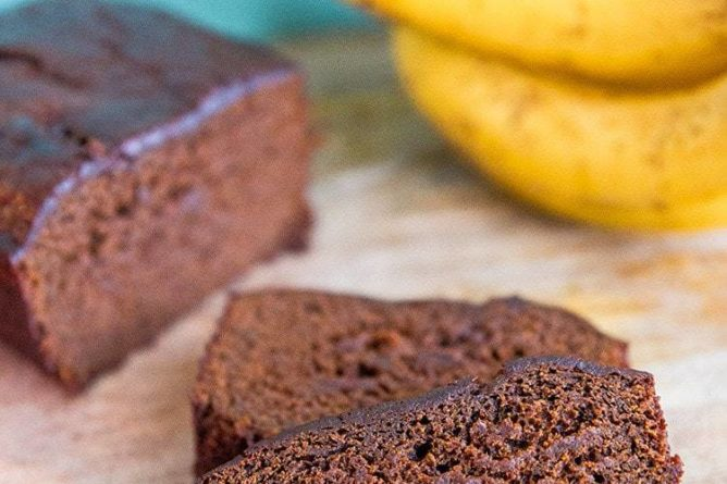 close up slices of Banana Gingerbread Loaf, ripe bananas on background
