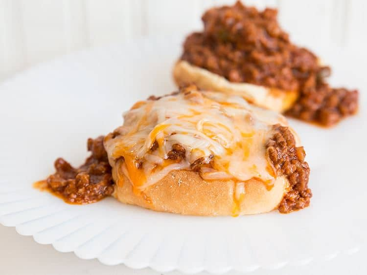 white plate with Sloppy Joes on top of hamburger buns topped with cheese
