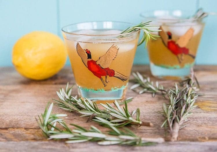 Maple Rosemary Bourbon Sour in a pheasant cocktail glasses, springs of rosemary and fresh lemon on background