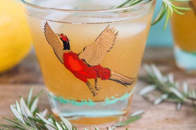 Maple Rosemary Bourbon Sour in a pheasant cocktail glasses with springs of rosemary