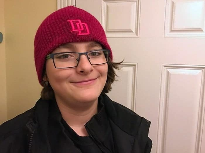young boy wearing black jacket and red beanie