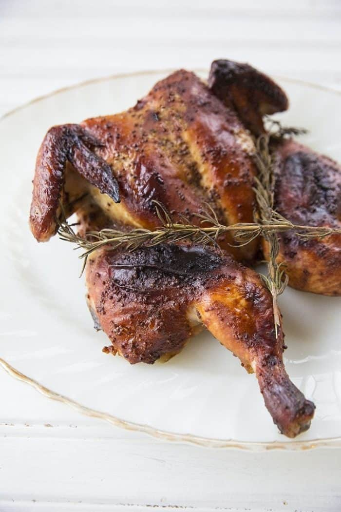 Honey Mustard Whole Chicken in White Plate with Rosemary Sprigs