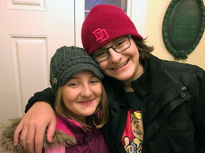 siblings smiling together - girl wearing pink jacket, boy wearing black jacket