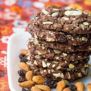 close up Old Fashioned Chewy Chocolate Raisin Cookies in a white plate with almonds and raisins