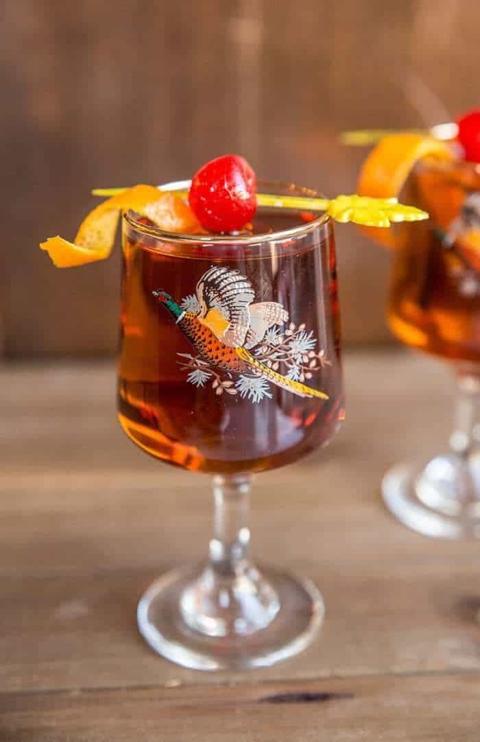 Manhattan cocktail drink in vintage pheasant glasses with cherry and orange garnish