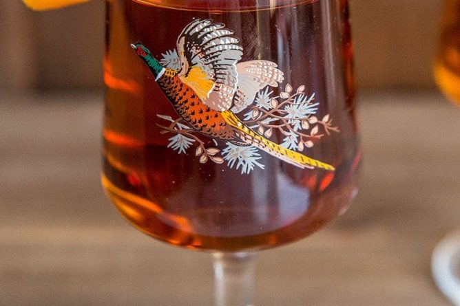 Close up of Manhattan cocktail drink in vintage pheasant glass with cherry and orange garnish