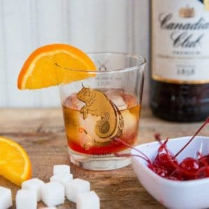 Old Fashioned Cocktail - whisky glass with sugar cube and maraschino cherry Garnish with an orange slice