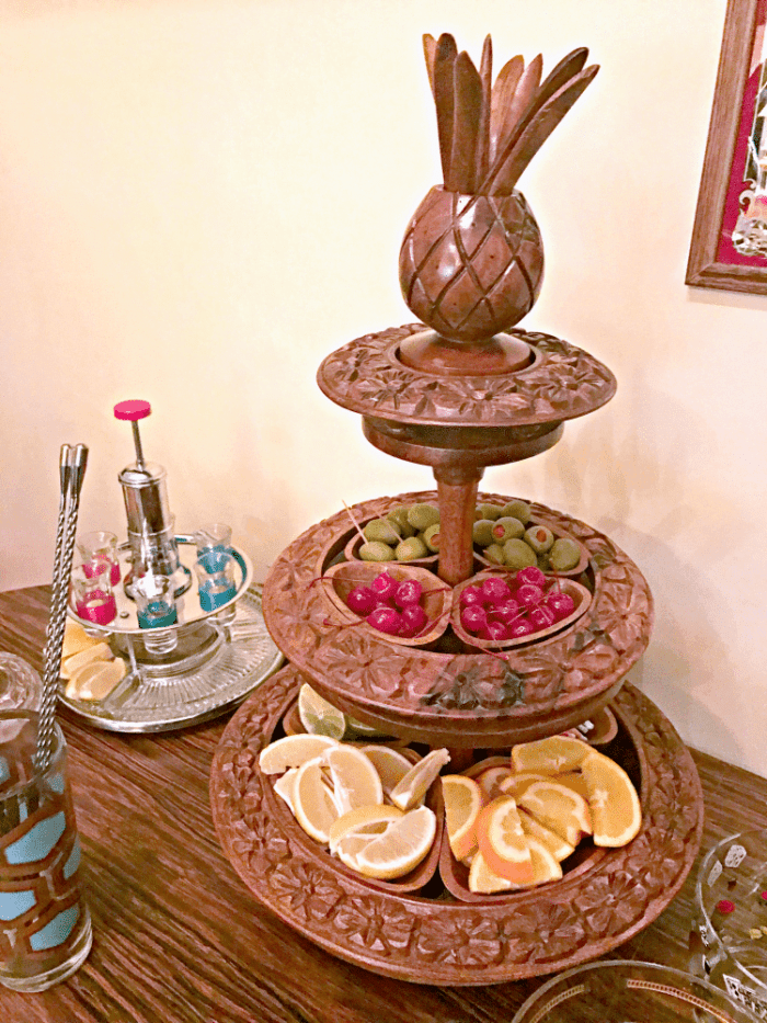 wooden pineapple serving tray with all the drink fixings in it - cherries, olives, little umbrellas and the fresh citrus.