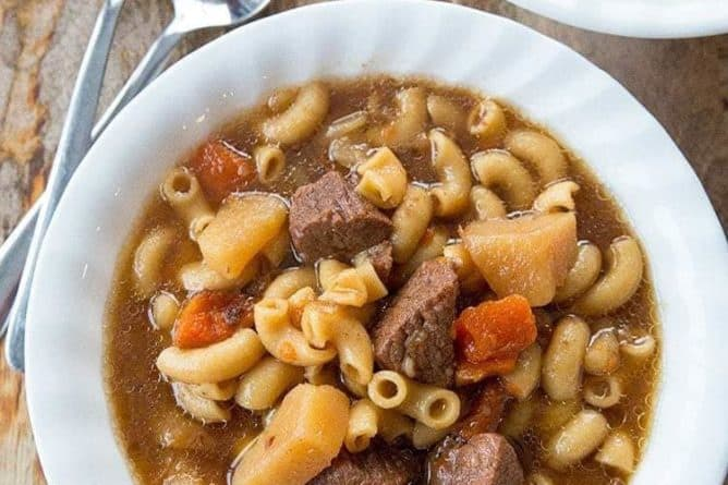 Top down shot of Beef Macaroni Soup in beef broth based on wood background