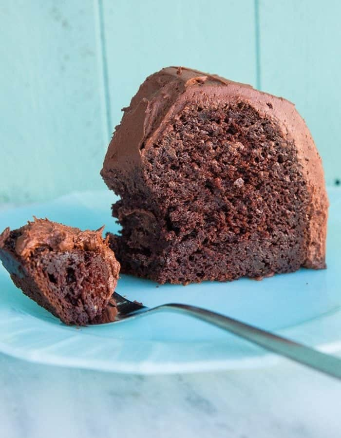 Close up of Chocolate Avocado Bundt Cake Slice with Chocolate Icing in a White Plate and on a Spoon