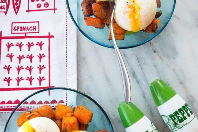 top down shot of Maple Roasted Butternut Squash on transparent plate topped with poached eggs