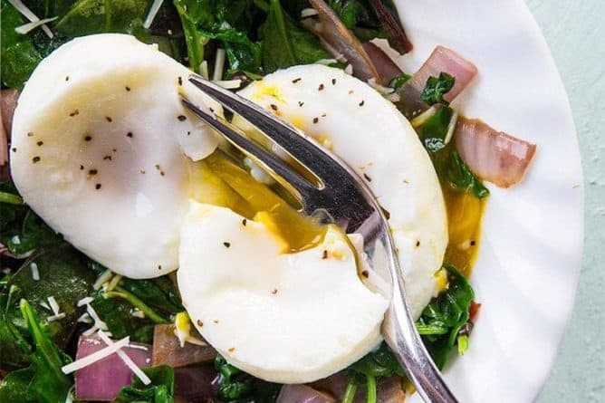 slicing the poached egg on top of Mixed Greens & Cajun Onions Vegetable Breakfast Goal Bowl
