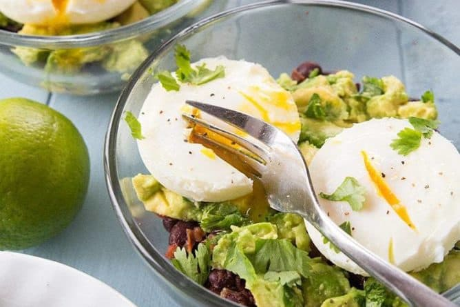 Kale Breakfast in transparent bowls topped with poached eggs on top