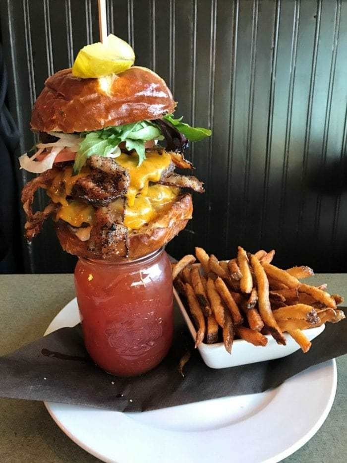 Bacon Double Alberta Beef Burger on top of a Bacon Caesar with fries on the side
