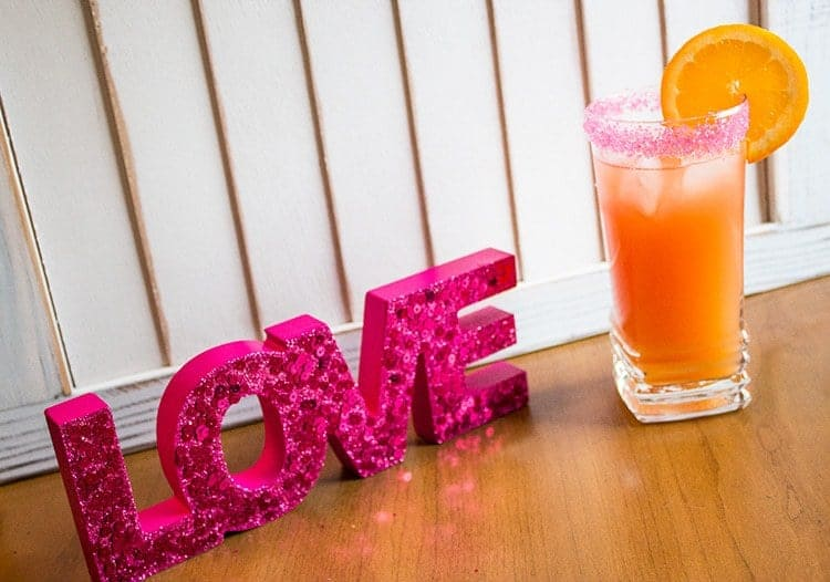 A Glass of Sex on the Beach Cocktail Garnish with Orange Slice, Pink LOVE lettering beside it