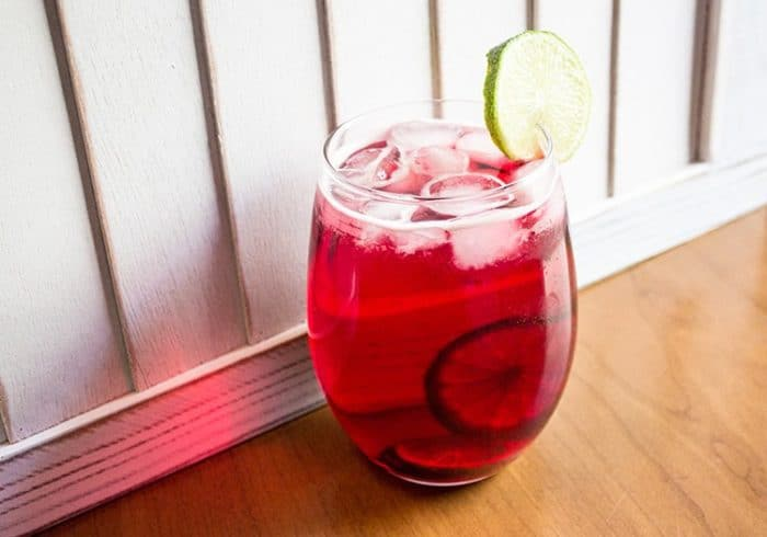 A Glass of Cranberry Zombie Drink with Slices of Lime