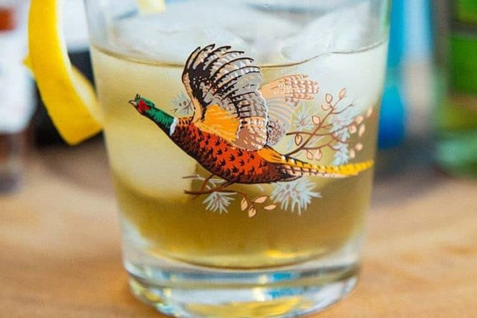 Close up of Bijou Cocktail in Pheasant glass garnish with twisted lemon peel