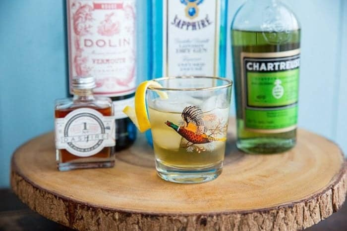 A glass of Bijou Cocktail in a round wood stand, bottles of dry Gin, Green Chartreuse, sweet Vermouth and orange bitters at the back