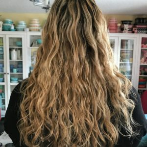 woman showing her long curly dark blonde hair hair