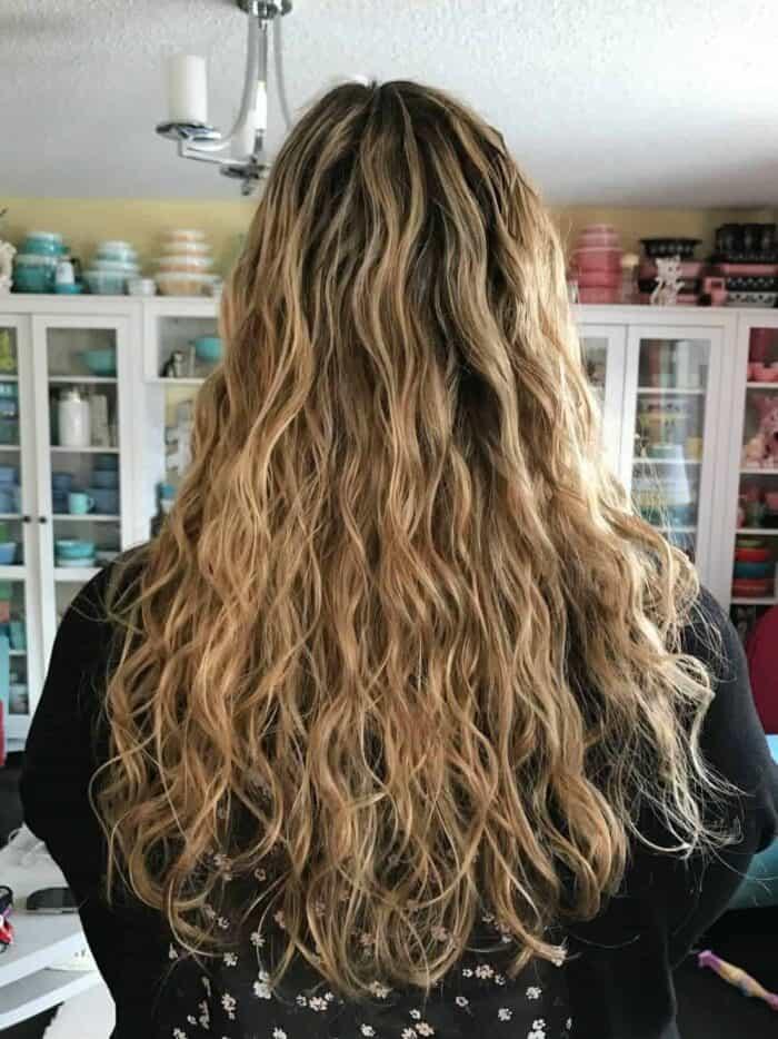 woman showing her long curly dark blonde hair hair