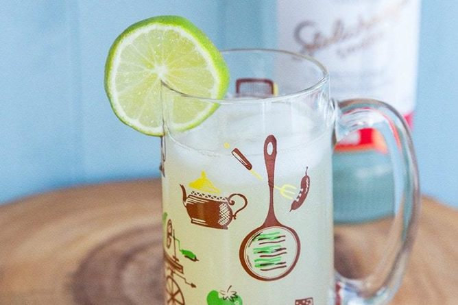 Classic Moscow Mule Recipe in a Vintage Hazel Atlas Glass, garnish with a slice of lime and a bottle of vodka on background