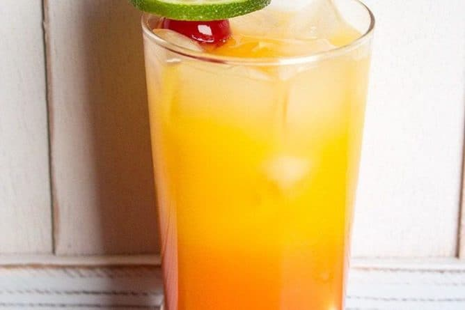 Close up of a glass with tequila sunrise garnish with a slice of lime and 2 maraschino cherries on pick