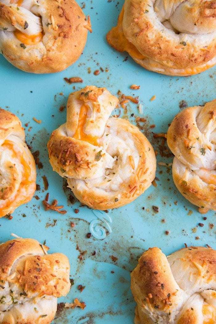 Top down shot of Cheese Stuffed Garlic Knots on jade blue background