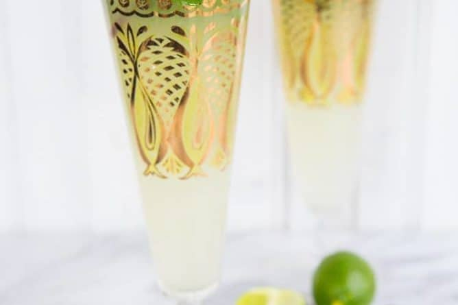 close up of Key Lime Mojito in pilsners with gold prints garnish with fresh mint and lime