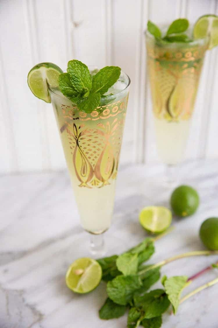 Key Lime Mojito in pilsners with gold prints garnish with fresh mint and lime on white background