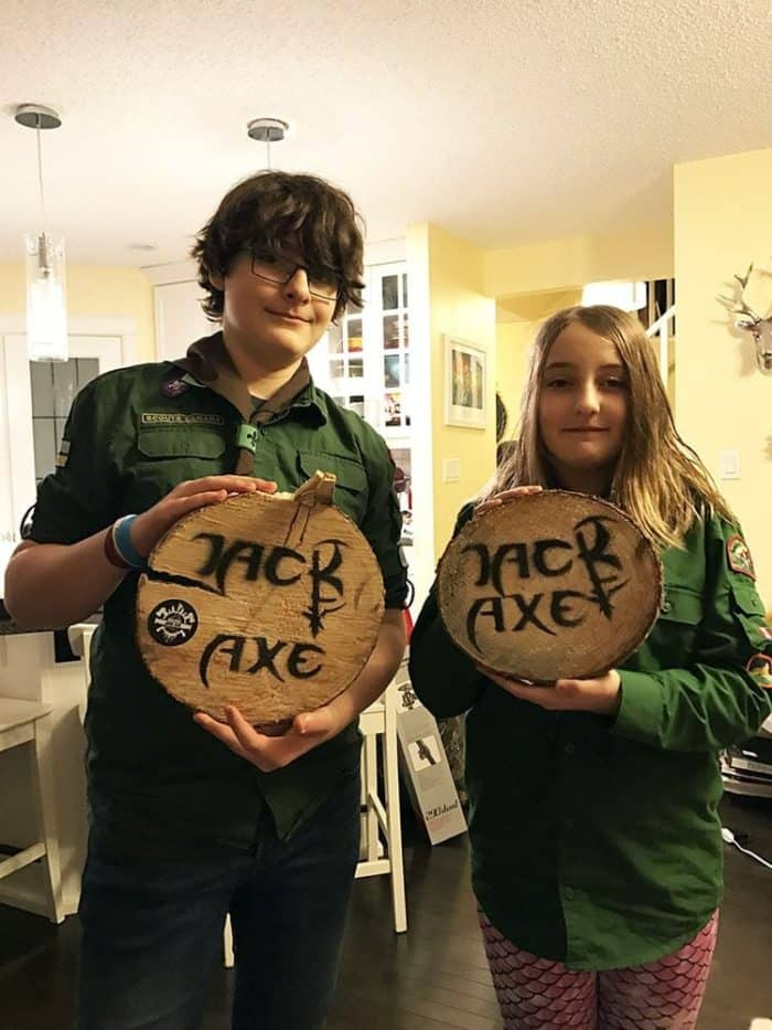 two kids holding log chunks with print of Jack Axe