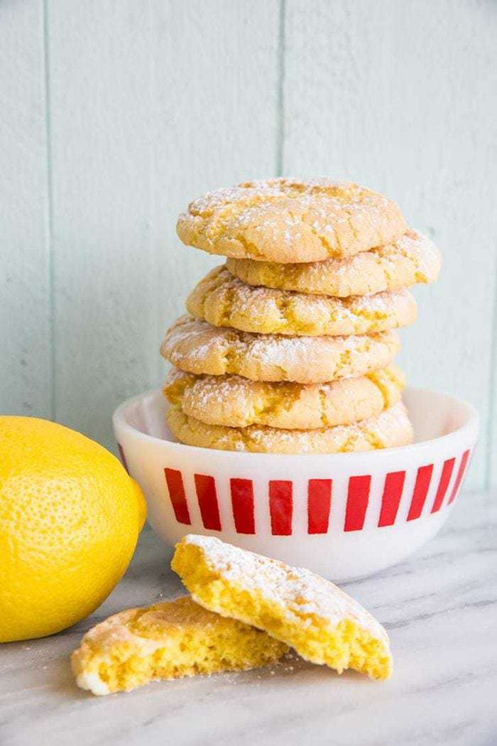 stack of Lemon Crinkle Cake Cookies in a white bowl with red prints, fresh lemon beside it