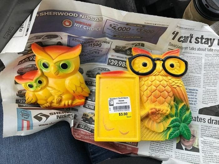 two pieces of Chalkware yellow colored owls on old news paper page