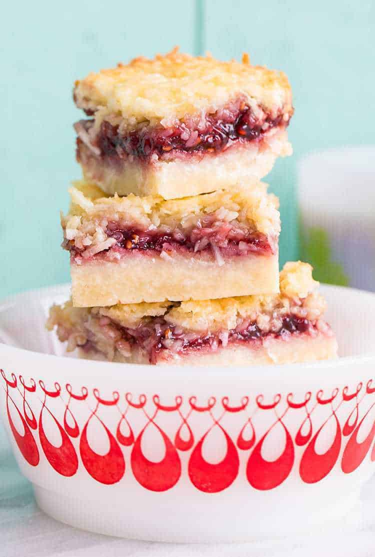 close up stack of Raspberry Coconut Bars in a white bowl