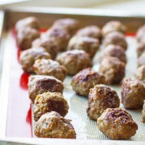 Close up of Rolled meatballs on a baking sheet