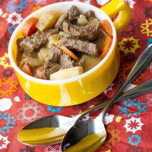 close up of savory venison stew in a yellow mug with potatoes and carrots, 2 spoons on the side