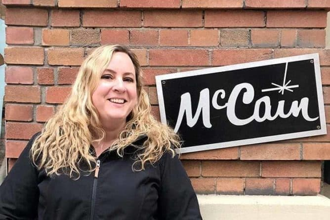 woman wearing black jacket standing near the McCain signage with brick wall on background