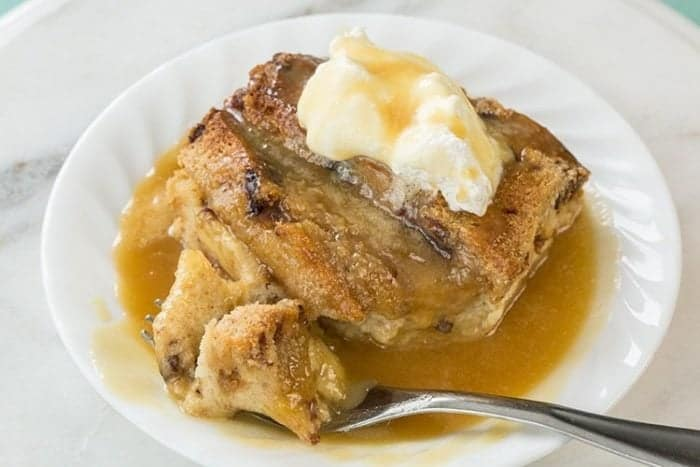 Delicious Bread and Butter Pudding in a white plate served with caramel sauce