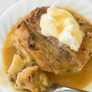 slices of Bread and Butter Pudding with caramel sauce in a white plate on marble background
